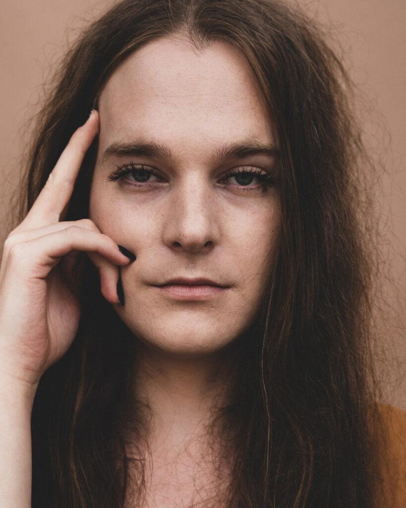 Nærbillede af ung person med langt hår og hånden på siden af hovedet.