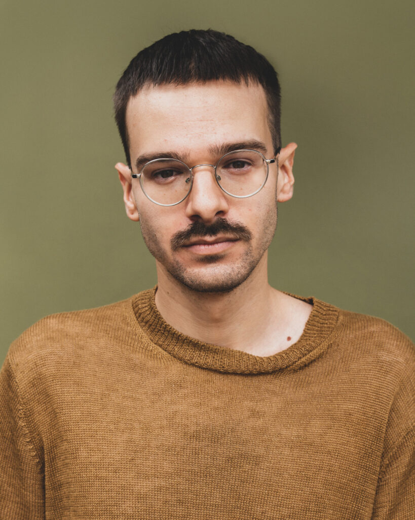 Portræt af yngre person med briller og skæg.