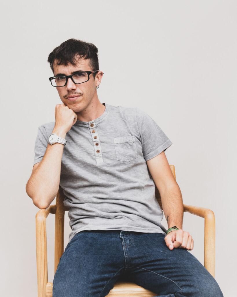 Person med briller og kort hår sidder i stol og læner den hovedet på den ene arm.