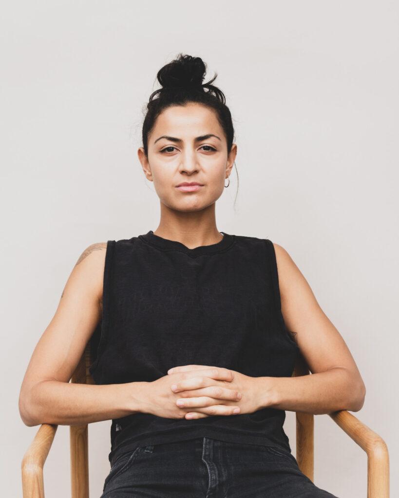 Yngre person i sort tøj sidder på stol og kigger lige i kameraet med foldede hænder.