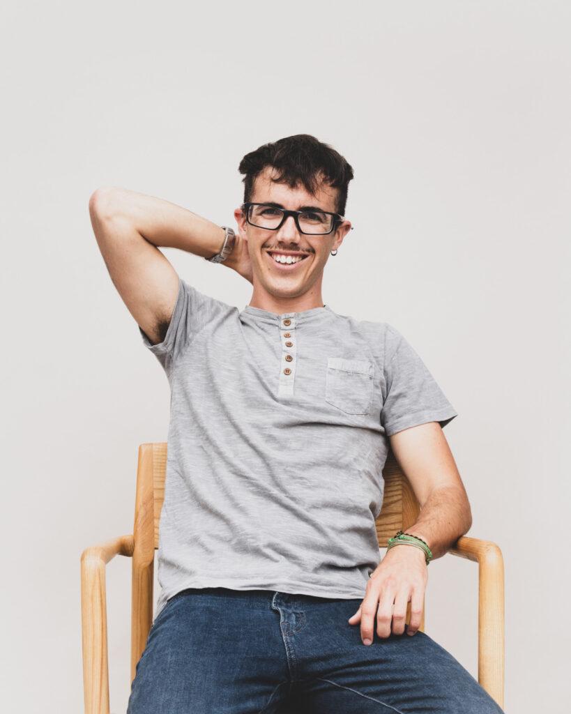 Yngre person med briller sidder på stol og smiler med den ene hånd bag hovedet.